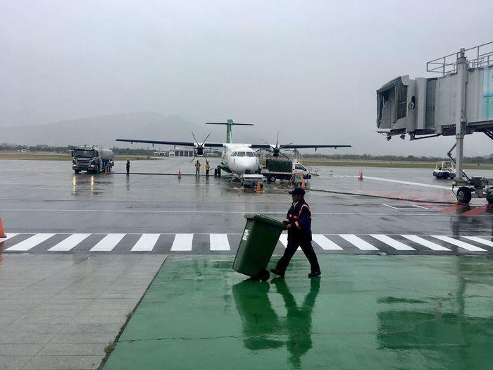 Man pushing garbage can at airport runway during rainy season