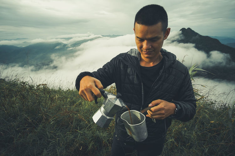 Man pouring black tea in jug while standing on field