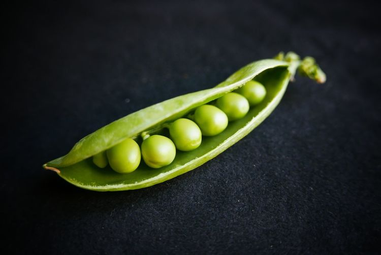 Close-up of open pea pods against black background
