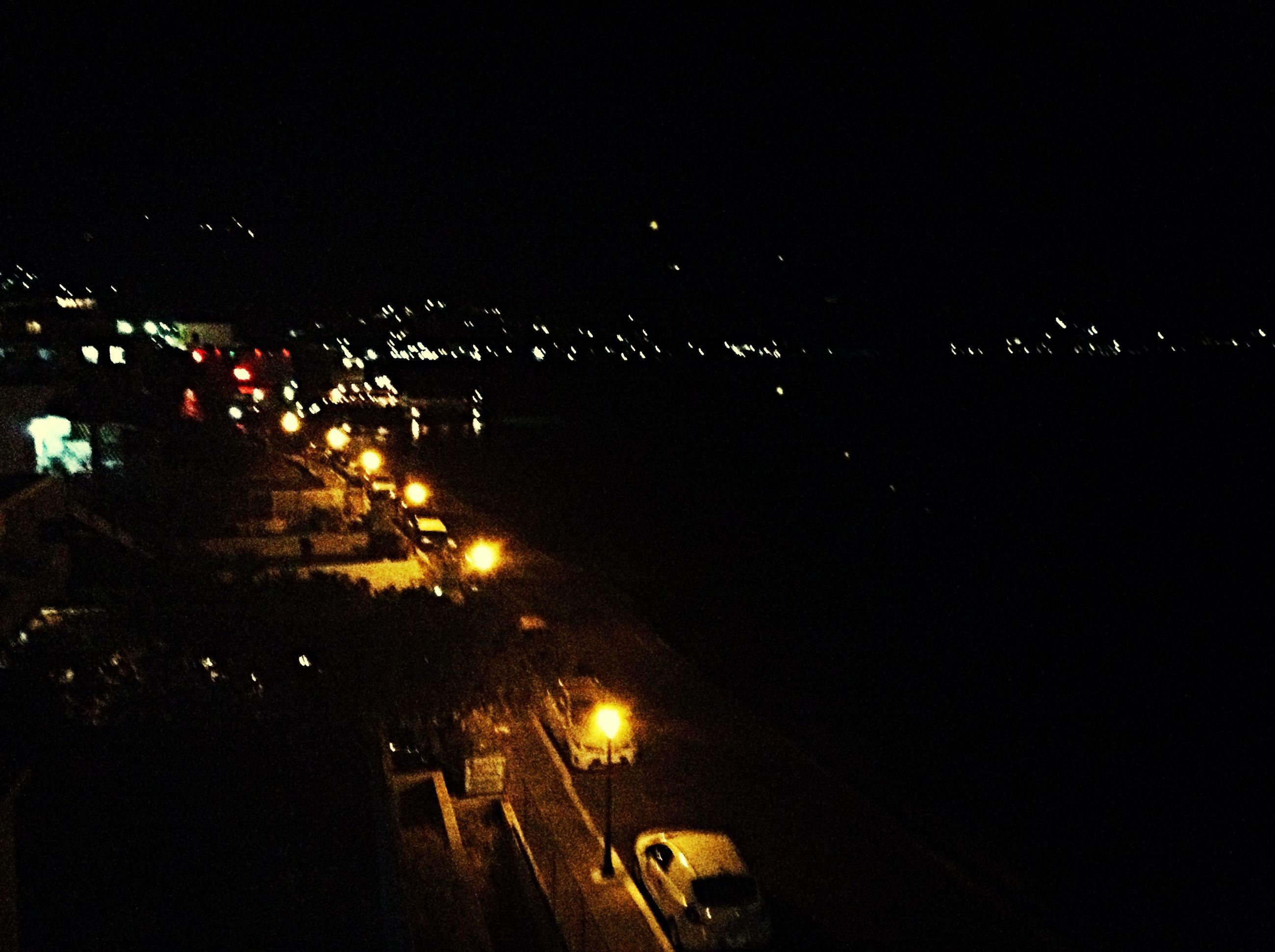 night, illuminated, street light, lighting equipment, city, light - natural phenomenon, dark, street, electricity, low angle view, sky, building exterior, glowing, outdoors, city street, silhouette, transportation, no people, motion, city life