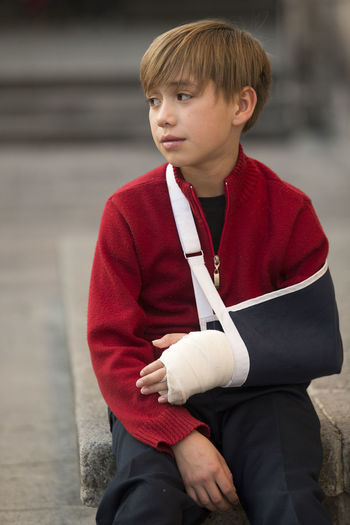 Smiling boy with orthopedic cast sitting outdoors