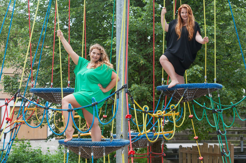 Portrait of happy friends posing on jungle gym