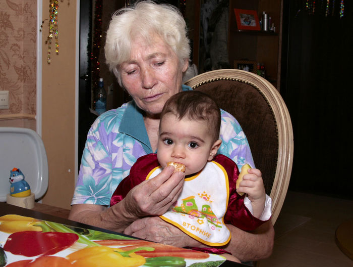 A grandma feeding grandchild Baby Childhood Cute Eating Elementary Age Enjoyment Family Feeding  Feeding Time Grandma Happiness Person Portrait