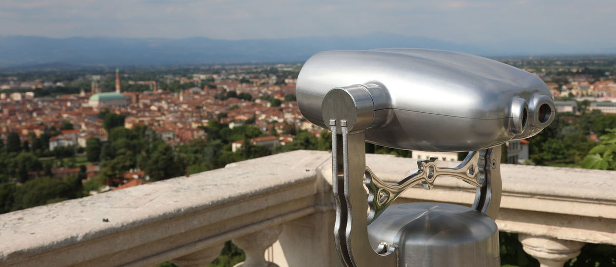 Close-up of coin-operated binoculars against cityscape