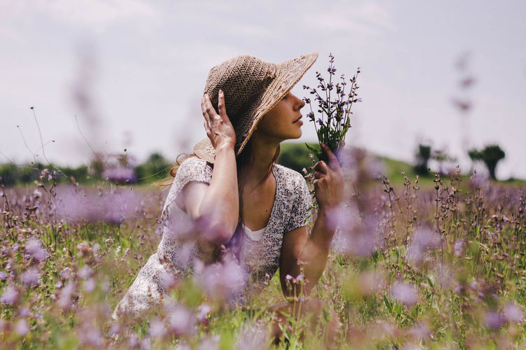 Woman Smelling Flowers On Field
