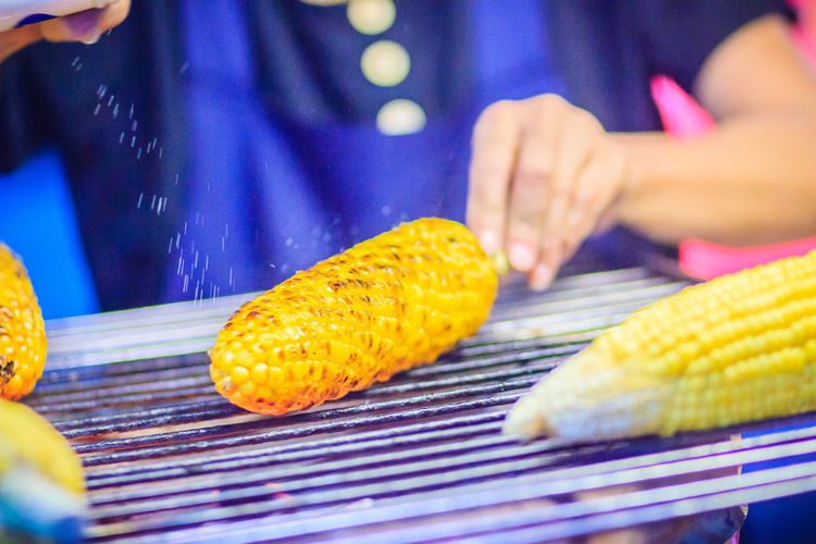 Close up hand of street food vendor while grilling for mixed sweet corn butter. Cook is grilling and sprinkling salt, sugar and butter to the grilled sweet corn on the electric stove. Grilled Corn Khao San Rd Khao San Road KhaoSan Khaosan Rd. Khaosandroad Barbecue Corn Finger Food Food And Drink Freshness Grilled Cornes Hand Holding Human Body Part Human Hand Khao San Khao San Knok Wua Khao San Rd. Khaosan Road Khaosanroad Lifestyles Men Midsection Night Market Night Market In Thailand Outdoors People Preparation  Preparing Food Real People Selective Focus Sprinkling Salt Sweetcorn Vegetable