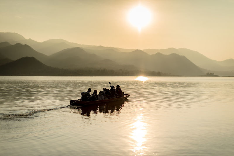 Nautical Vessel Water Transportation Mode Of Transportation Mountain Sky Group Of People Beauty In Nature Scenics - Nature Real People Waterfront Nature Lake Silhouette Mountain Range Sun Men Sunset Lifestyles Outdoors