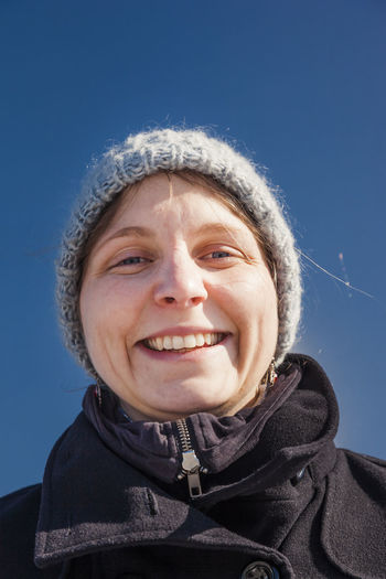 Close-up portrait of smiling woman wearing knit hat during winter