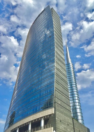Low angle view of modern glass building against sky