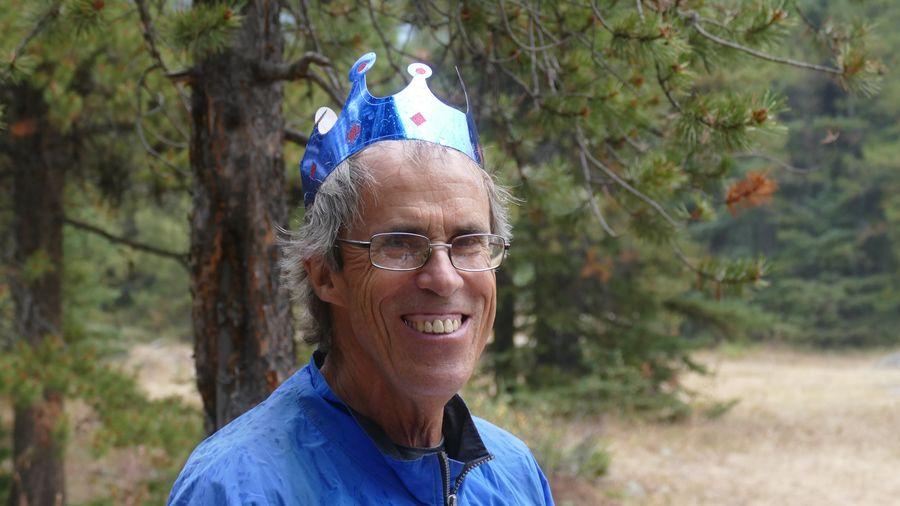 Portrait of smiling senior man wearing crown against trees