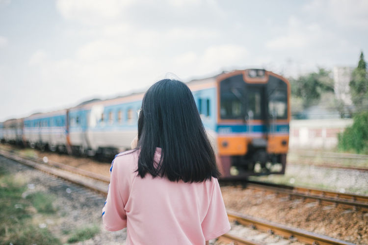 Rear view of woman with train at railroad station platform