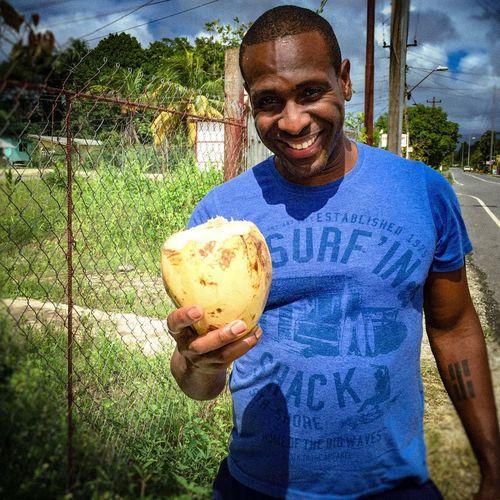 Man holding a coconut in Trinidad. Sunny Coconut Trinidad And Tobago Trinidad Caribbean Urban Black Male Male Grass Filmgrain