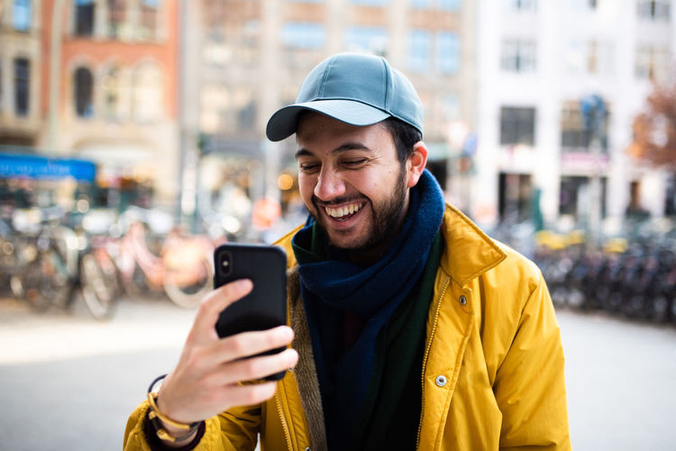 Happy young man using mobile phone in city