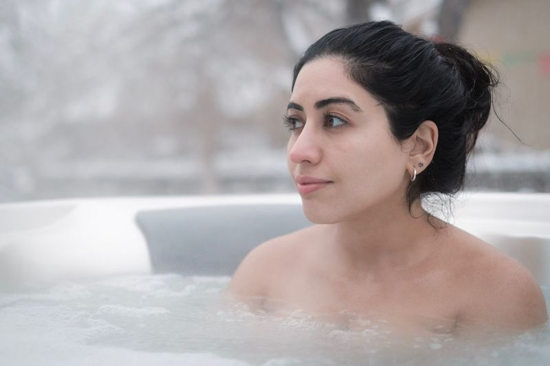 Close-up of thoughtful woman in hot spring looking away