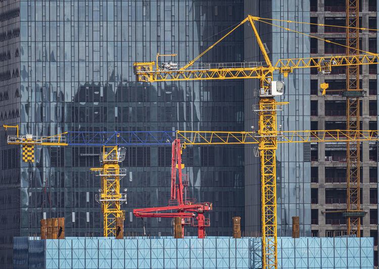 Crane at construction site against buildings in city