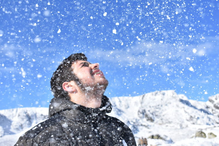 Close-Up Of Young Man During Snow Fall