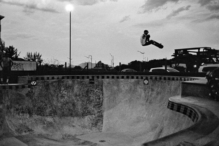 Man skateboarding on skateboard against sky