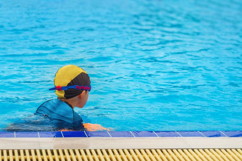 Boy swimming in blue pool
