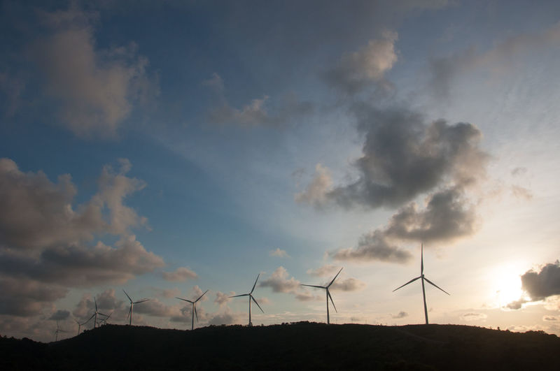 Wind turbines on land against sky during sunset
