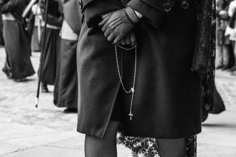 Midsection of woman holding praying beads while standing on street