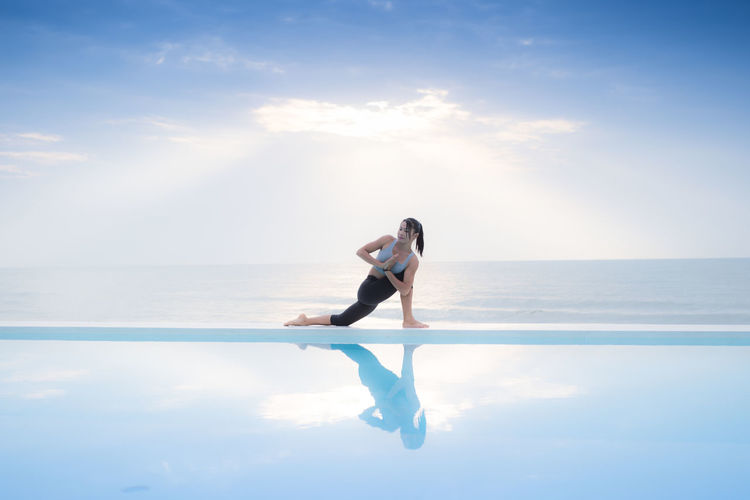 Full Length Of Young Woman Exercising By Infinity Pool Against Sea Against Sky