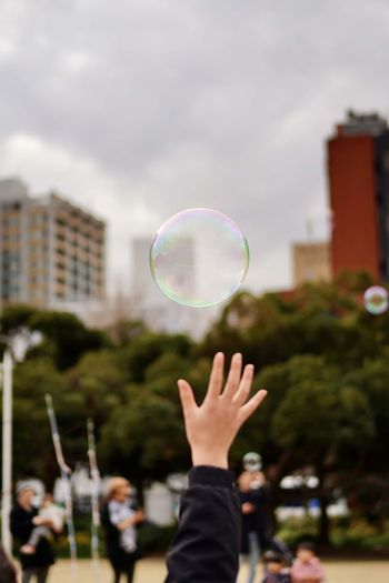 Cropped hand of woman reaching to bubble at park