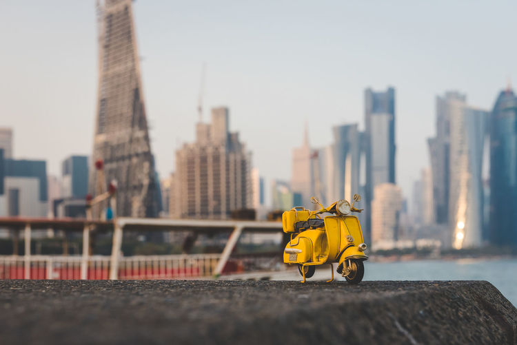 Miniature hand made toy scooter. Architecture Built Structure Building Exterior City Sky Nature Yellow Transportation Day Building Outdoors Skyscraper Travel Urban Skyline Focus On Foreground Cityscape Office Building Exterior Tall - High No People Mode Of Transportation Financial District  Scooter Vespa Toy