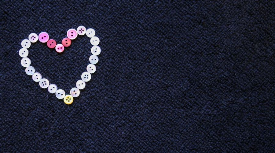 Close-Up Of Buttons Arranged In Heart Shape On Table