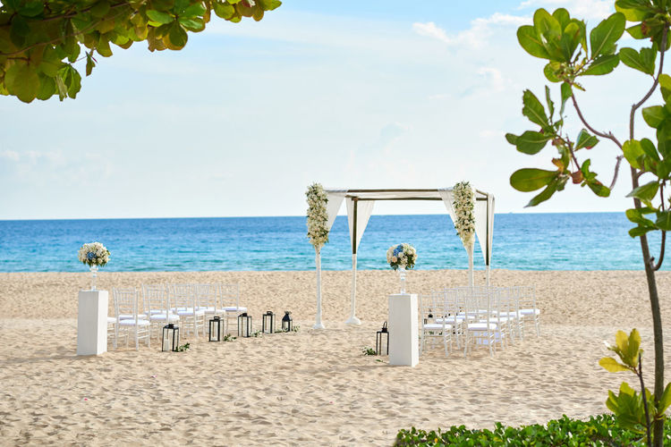 Wedding ceremony venue setup for small size on the beach, white sand with ocean in background, clear sky, minimal flowers, floral decoration for arch. Tree in foreground. Banquet Celebration Coastline Nature Panoramic Phuket Romantic Thailand Wedding Arch Beach Ceremony Decoration Flower Honeymoon Island Marriage  Ocean Outdoors Samui Sand Scenics Sea Sunset Tropical