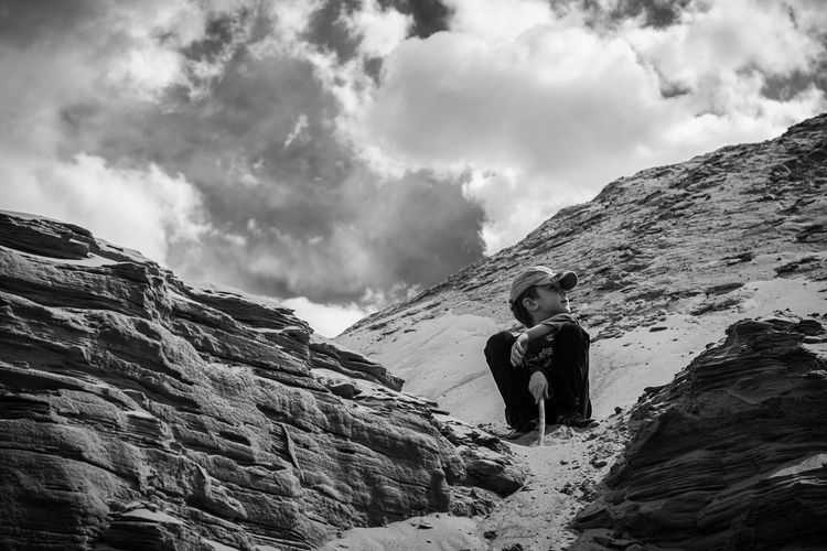 Low angle view of child standing on mountain against sky