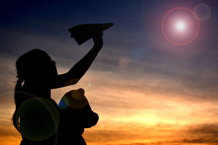 Silhouette girl holding paper airplane against sky during sunset