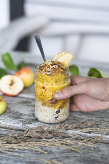 Cropped image of hand holding jar with apple porridge on table