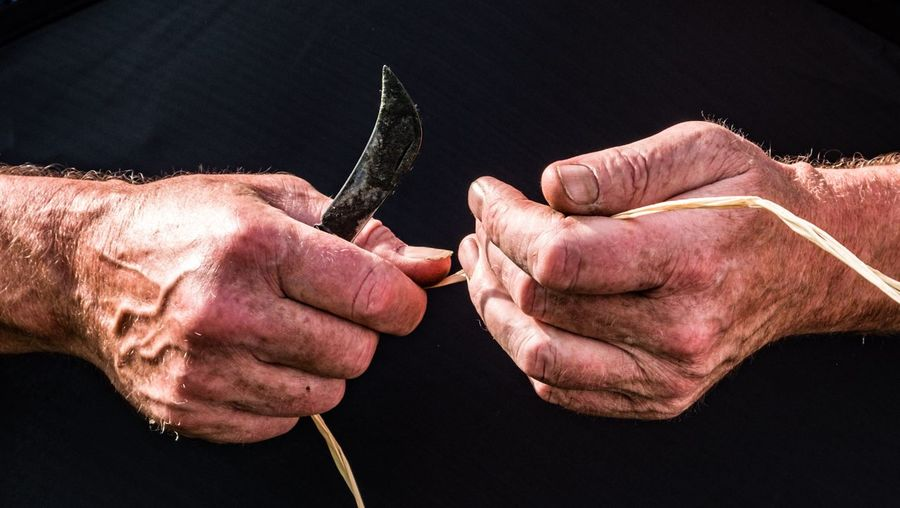 Midsection of man holding string and knife