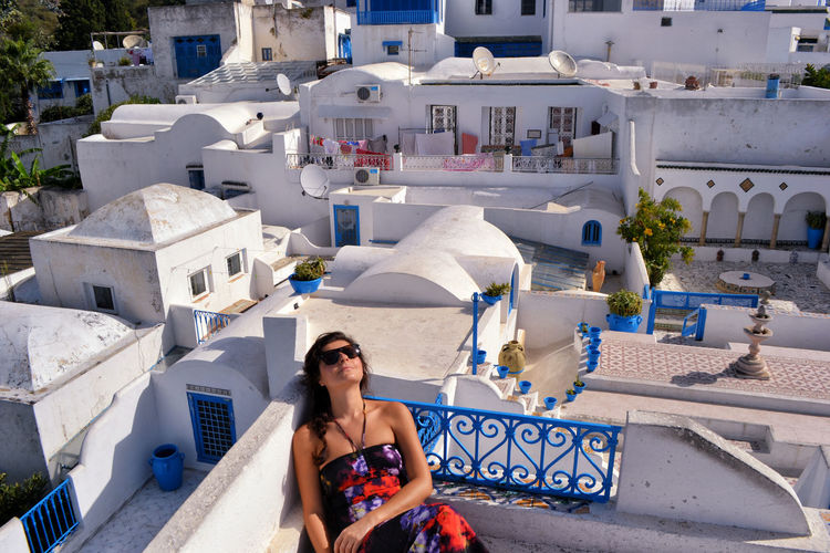 High angle view of mid adult woman wearing sunglasses while sitting on building terrace