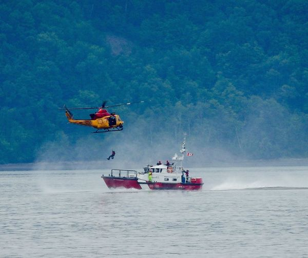 Helicopter above coast guard boat