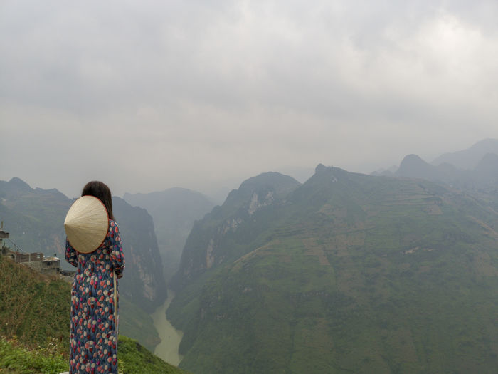 Young Vietnamese women facing and pose for camera with stunning view of the Nho Que river surrounded by mountains from the Ma Pi Leng pass in northern Vietnam Mountain Cloudy Green Color Meo Vac Vietnam Vietnamese Ao Dai Beauty In Nature Cloud - Sky Day Environment Landscape Leisure Activity Lifestyles Looking At View Mountain Mountain Range Nature Non-urban Scene One Person Outdoors People Pose Real People Rear View Scenics - Nature Sky Standing Sunrise Traditional Dress Tranquil Scene Tranquility Valley Women