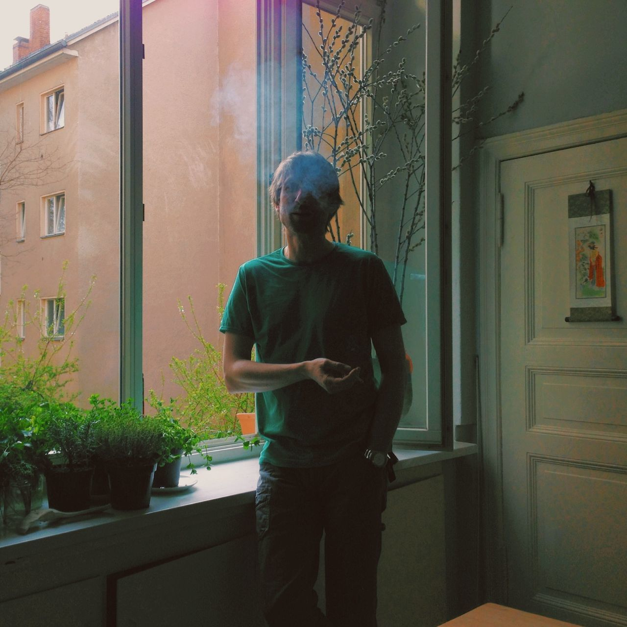 Serious young man smoking by the window