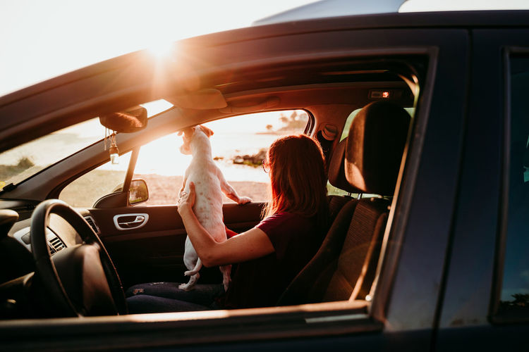 Woman sitting in car with dog during sunset