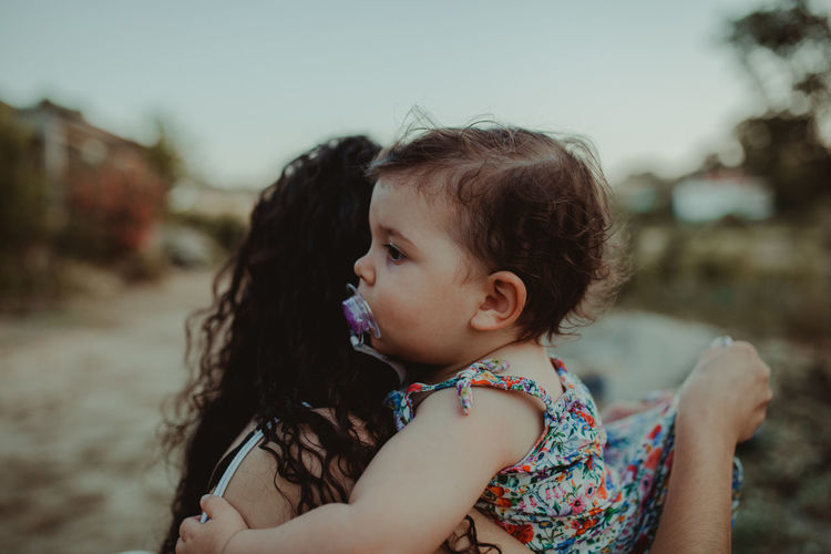 Side view of mother carrying cute daughter against sky