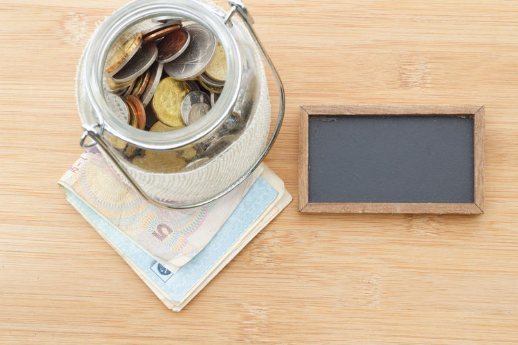 Financial concept Concept Conceptual Money Money Money Money Glass Jar Savings Saving Fund Loan  Debt Budget Copy Space Copyspace Directly Above Table High Angle View Wood - Material Close-up