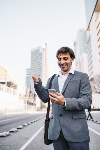 Low angle view of businessman using smart phone while standing on road