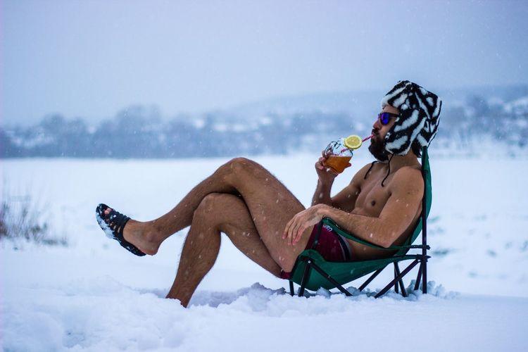 Shirtless man drinking while sitting on sled during winter