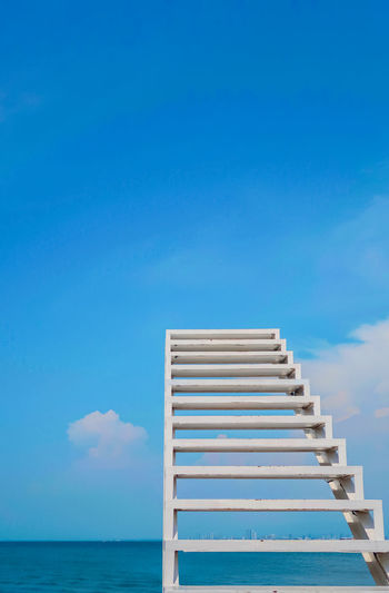 Low angle view of ladder by sea against blue sky
