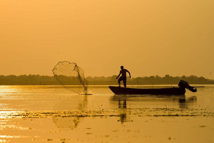 Silhouette fisherman fishing in lake against clear orange sky