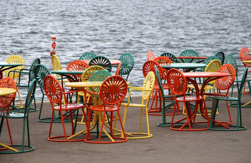 Colorful chairs on walkway against sea