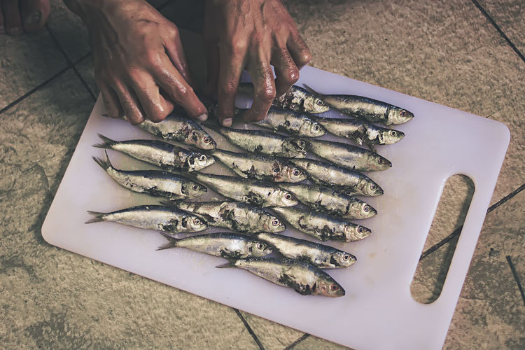 High Angle View Of Cropped Hand Arranging Fish On Cutting Board