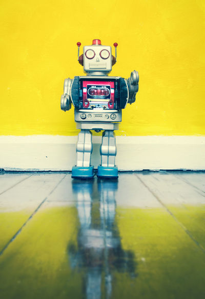 retro silver robot on a wooden floor Bright Colors Copy Space Ray Gun Retro Standing Close-up Flooring Futuristic Hi Indoors  No People Reflection Retro Styled Robot Silver Colored Technology Tin Toys Toy Toy Photography Vintage Toys Yellow