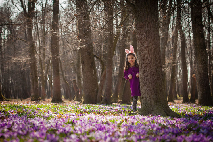 Portrait of woman with purple flowers in forest