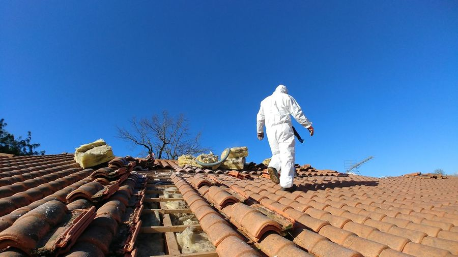 Man walking on roof tiles against clear blue sky