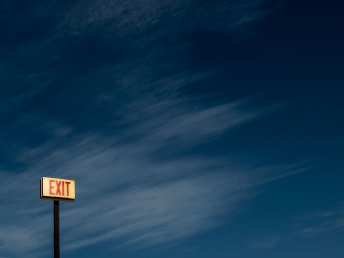 Low angle view of red exit sign against blue sky